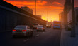 cars are driving along the highway road in the city to meet the sunset