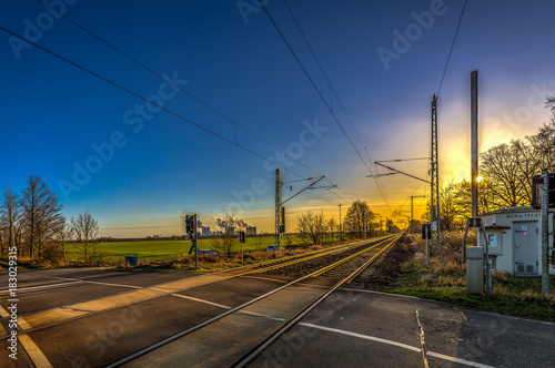 Fotografia, Obraz  Beautiful blue and yellow sunset on level crossing, double track with passing tr