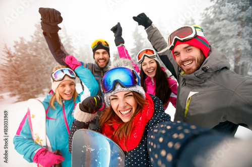 Group of cheerful friends with ski on winter holidays - Skiers having fun on the snow