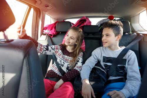 Winter holiday, ski, travel - kids enjoying in traveling to ski resort making selfie