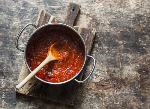 Fotografia Classic homemade tomato sauce in the pan on a wooden chopping board on brown background, top view
