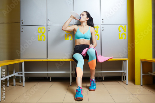 Fit young woman in activewear sittingin sports dressing room and drinking water from plastic bottle