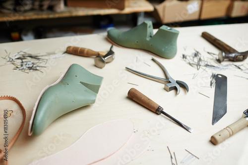 Shoe workpieces and handtools of cobbler on table of shoemaker