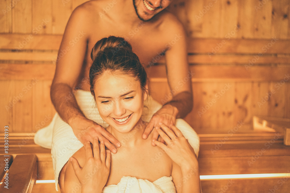 Fototapeta Young happy couple relaxing inside a sauna at spa resort hotel luxury - Romantic lovers having a bodycare day in steam bath man making a massage for his girlfriend - Relax, love, lifestyle concept