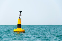 Floating Yellow Buoy On Blue Sea