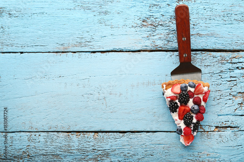 Valokuva  Slice of tart with berries on blue wooden table