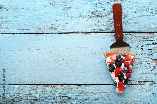 Fotografia, Obraz  Slice of tart with berries on blue wooden table