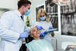 Beautiful senior woman at dentist office having dental treatment.