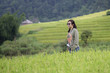 Woman walking with her camera in the rice field.