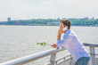Wearing white shirt, jeans, holding white rose, a young guy standing by Hudson River in New York, opposite New Jersey, listening, talking on mobile phone. Concept of looking for love, friendship..