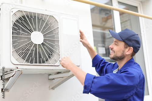 Fotomural  Male technician repairing air conditioner outdoors