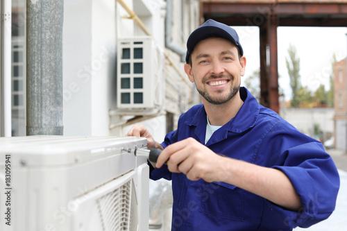 Fotografía Male technician repairing air conditioner outdoors
