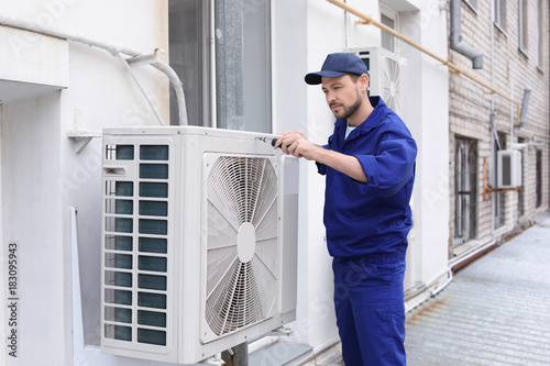 Cuadros en Lienzo  Male technician repairing air conditioner outdoors