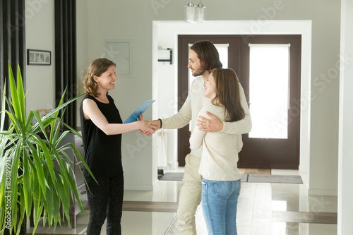 Obraz Friendly realtor and young couple shaking hands standing in hallway, real estate agent handshaking clients at meeting, showing selling buying property for rent sale, discussing deal with customers - fototapety do salonu