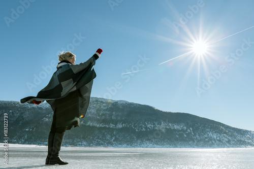 Tuinposter Wintersporten woman enjoying beautiful day on frozen lake