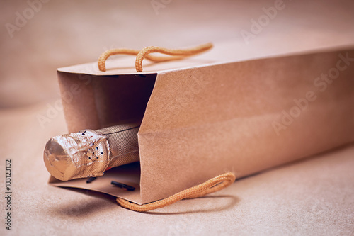 Sparkling wine in craft gift bag on abstract craft paper background