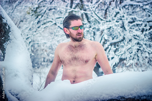 Photo  Naked wild man with sunglasses at winter snowy forest