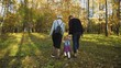 Lovely parents with their little daughter walking in autumn park. 4K