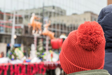 A Woman Wearing A Red Hat Watc...
