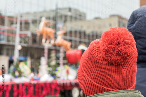 Fotografie, Obraz A woman wearing a red hat watching  a Santa Christmas parade