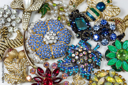 Photo Collection of colorful vintage rhinestone brooches, on white, horizontal aspect