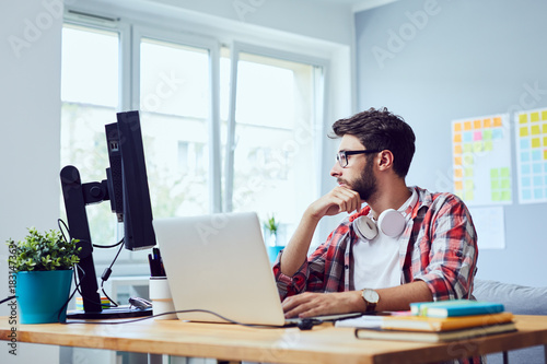 Fotografía  Focused young man thinking about his start-up business while looking at screen i