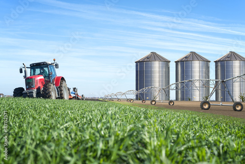 Obraz Concept of agriculture food chain production with watering system and silos. - fototapety do salonu