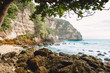 Tropical blue ocean with waves and rocky cliff in Bali. Paradise place in tropics