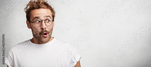 Horizontal shot of amazed bearded male has European appearance wears spectacles, Canvas Print