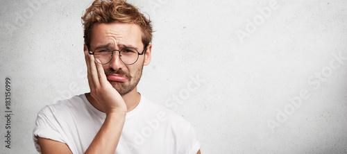 Fotografia  Discontent sorrorful male has terrible toothache, can`t stand pain, being upset, poses against white background with copy space for your advertising content