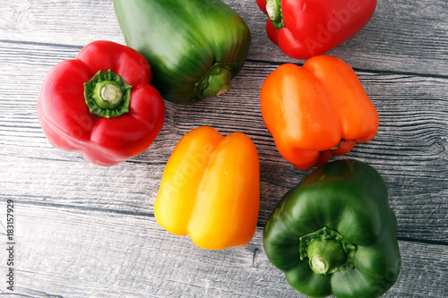 Fotografia Red, green and yellow sweet bell peppers on table.