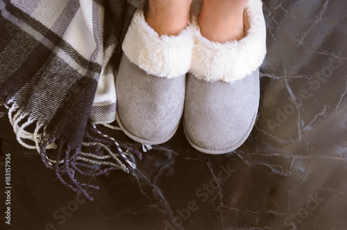 Obraz Female legs in cozy slippers on mramor  floor with cashmere blanket. Woman wearing  warm and comfortable slippers on the morning. Relax and stay at home concept. Copy space. - fototapety do salonu
