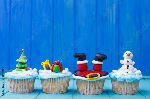 Photo  Delicious New Year or Christmas cupcakes set with bright decorations made of confectionery mastic