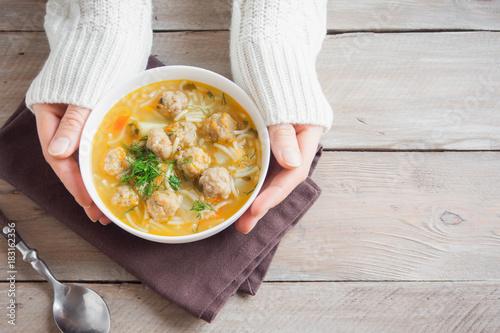 Meatball soup in hands