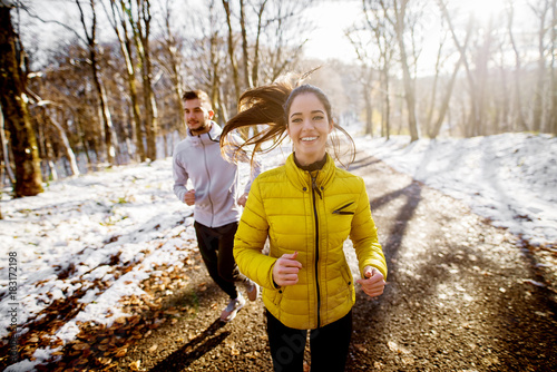Poster Glisse hiver Smiling beautiful young healthy girl running with a trainer in sportswear through the forest in the sunny winter morning.
