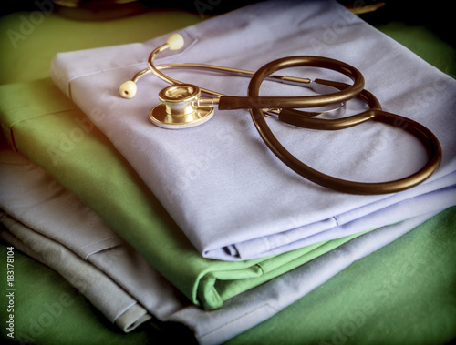 Fotografía  Stethoscope about blue and green nurse uniform in a hospital, conceptual image