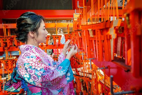 Fotografia Women in traditional japanese kimonos at Fushimi Inari Shrine in Kyoto, Japan
