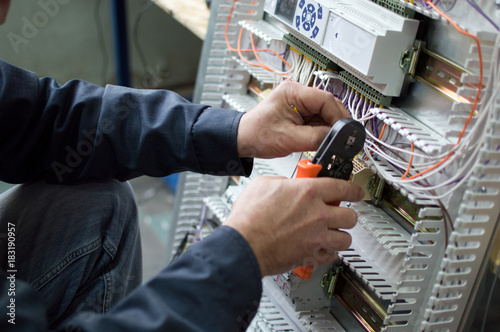Hands of electrician assembling industrial HVAC control cubicle in ...