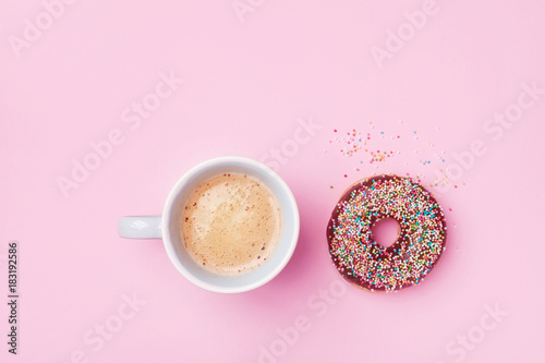 Morning coffee cup and sweet pastry of chocolate donut on pink pastel table top view. Flat lay. Cozy breakfast.