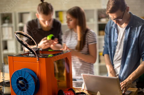 Group of creative designers working together, using 3D printer in modern studio and discussing project, focus on printing machine in foreground