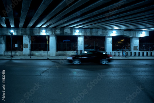 Photo  Gritty dark Chicago highway bridge and city street with a passing black car and bicycle stand at night