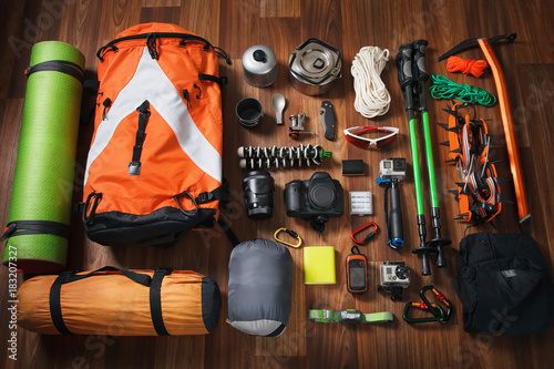 climbing equipment: rope, trekking shoes, crampons, ice tools, ice ax, ice screws, set on dark wooden background, top view Fototapete