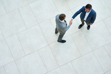 Top View Of Two Business People Shaking Hands Standing On Tiled Floor In Hall Of Modern Office Building, Copy Space