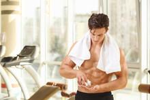 Muscular Young Man Taking Pill...