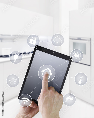 home automation hand touch screen digital tablet with symbols on kitchen blurred background