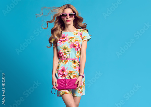 Fashion. Blond Woman in fashion pose. Young beauty Lady in Floral Dress Blowing lips. Trendy fashion Hairstyle, Glamour Pink Clutch. Playful Girl, Spring Summer Outfit