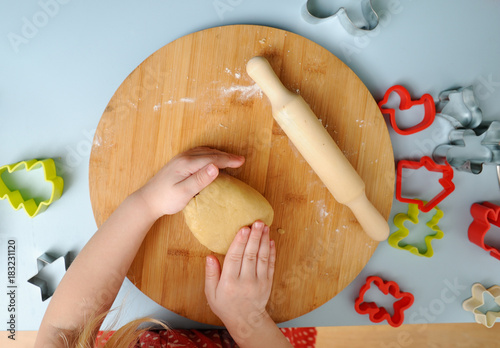 Cooking with children. Child kneading cookie dough for making cookies with cookie cutters