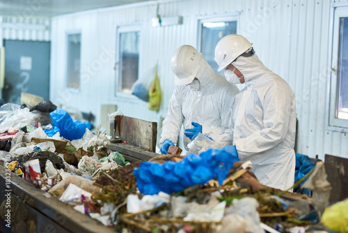 Fotografija  Portrait of two workers  wearing biohazard suits and hardhats working at waste p