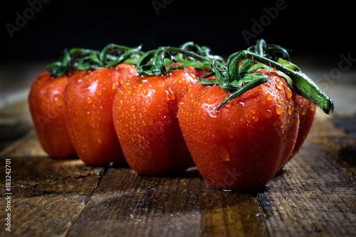 Photo  Rosa on tasty Italian tomatoes, wooden table