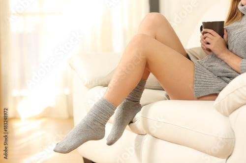 Obraz Woman wawed legs on a sofa in winter - fototapety do salonu